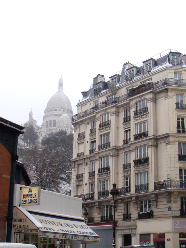 A view of the Sacre-Coeur with a fabric store to the left an a yarn shop on the right corner. Best view in Paris?